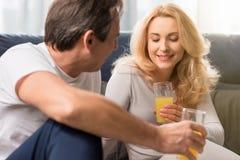 Le milieu a vieilli des couples tenant des verres avec le jus d'orange sur le lit Photos stock