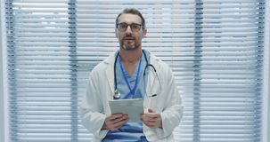 Le milieu a vieilli le docteur masculin utilisant le comprimé et parler à la caméra 4k banque de vidéos