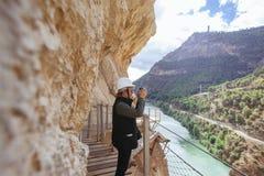 Le milieu a vieilli et femme aventureuse avec le casque prenant des photos sur une falaise Image libre de droits