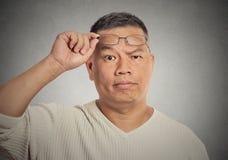 Le milieu a vieilli l'homme avec des verres vous regardant avec scepticisme Photographie stock