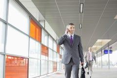 Le milieu a vieilli l'homme d'affaires à l'appel tout en marchant dans la gare Photographie stock libre de droits