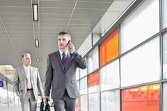 Le milieu a vieilli l'homme d'affaires à l'appel tout en marchant dans la gare photo libre de droits