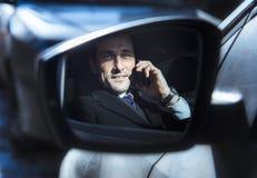 Le milieu a vieilli l'homme d'affaires parlant au téléphone, dans propre voiture Photo stock