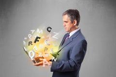 Le milieu a vieilli l'homme d'affaires tenant l'ordinateur portable avec les lettres colorées Image stock