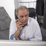 Le milieu a vieilli l'homme parlant dans le téléphone dans le bureau Photos stock
