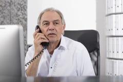 Le milieu a vieilli l'homme parlant dans le téléphone dans le bureau Photos libres de droits