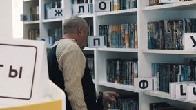Le milieu a vieilli l'homme reprenant réserve des caisses de livre de bibliothèque banque de vidéos