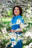 Le milieu a vieilli la femme avec le cerisier de floraison dans le jardin Photos stock