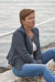 Le milieu a vieilli la femme caucasienne s'asseyant sur la plage de mer Photographie stock libre de droits