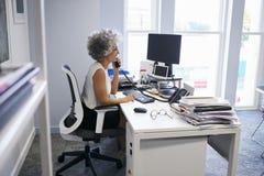 Le milieu a vieilli la femme d'affaires à l'aide du téléphone dans son bureau image stock