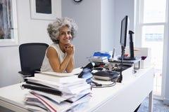Le milieu a vieilli la femme d'affaires souriant à l'appareil-photo dans son bureau photo stock