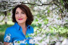 Le milieu a vieilli la femme dans le jardin d'été avec le cerisier de floraison Images stock