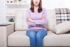 Le milieu a vieilli la femme s'asseyant sur le fond de sofa à la maison Copiez le jour de l'espace et de mères Ménopause et suivr Photo libre de droits