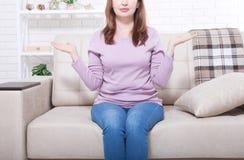 Le milieu a vieilli la femme s'asseyant sur le fond de sofa à la maison Copiez le jour de l'espace et de mères Ménopause et suivr Photographie stock libre de droits