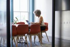 Le milieu a vieilli la femme seul travaillant dans la salle de réunion de bureau photos stock