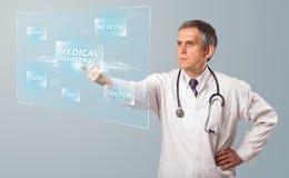 Le milieu a vieilli le docteur appuyant le type médical moderne de bouton Photographie stock libre de droits