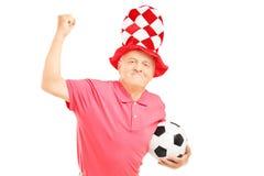 Le milieu a vieilli le supporter avec le chapeau tenant un ballon de football et un gesturi Image libre de droits