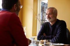 Le milieu a vieilli les couples masculins gais prenant le déjeuner dans un restaurant Photos stock
