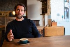 Le milieu a vieilli le mâle caucasien s'asseyant à la table en substance de explication de café images stock