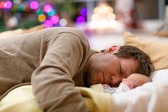 Le milieu a vieilli le père dormant près de sa fille nouveau-née de bébé sur Noël Photo stock