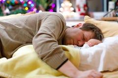 Le milieu a vieilli le père dormant près de sa fille nouveau-née de bébé sur Noël Images libres de droits