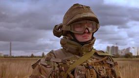 Le militaire caucasien puissant jette un coup d'oeil sur la caméra calmement tout en se tenant au milieu du champ de blé d'isolem banque de vidéos