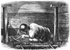 Le mineur extrait le charbon profondément sous terre image stock