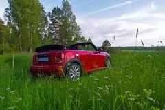 Le mini cabrio pendant l'été s'est garé dans l'herbe Photo libre de droits