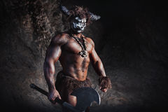 Le minotaur fâché d'homme de bodyart avec la hache en caverne Photos stock