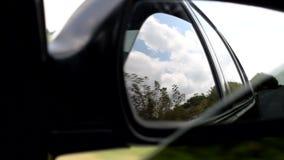 Le miroir de la voiture, qui montre le ciel et la route banque de vidéos