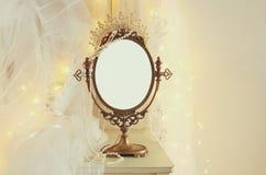 Le miroir ovale de vieux vintage et la beaux robe et voile de mariage blancs sur la chaise avec la guirlande d'or s'allume image stock