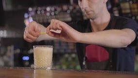 Le mixologist de barman après préparation d'un cocktail d'alcool avec différentes boissons le décorent avec le citron dans beau clips vidéos