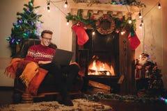 Le mâle heureux fait un achat sur l'Internet par l'intermédiaire d'un ordinateur portable Image stock