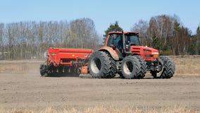 Le mêmes tracteur agricole et semoir sur le champ au ressort Images libres de droits