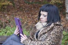 Le modèle alternatif s'est reposé sur un banc avec une tablette Photo libre de droits