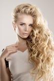 Le modèle avec de longues vagues de blonde de cheveux courbe le salon de coiffure Upd de coiffure Images stock