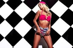Le modèle blond dans le style de rnb vêtx avec la casquette de baseball colorée rose Images libres de droits