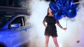 Le modèle chic dedans avec les supports gonflables de ballons près de la voiture en brouillard parmi le vol miroite clips vidéos