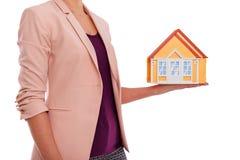 Le modèle de la maison est dans des mains femelles Images stock
