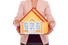 Le modèle de la maison est dans des mains femelles Image stock