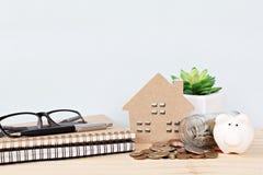Le modèle de maison en bois, tirelire, pièces de monnaie a dispersé du pot, des carnets, du stylo et des lunettes en verre sur le photographie stock libre de droits