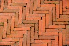Le modèle diagonal moussu du trottoir de brique dans un style en arête de poisson pour le fond, de vieilles briques oranges a cou photographie stock libre de droits