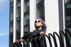 Le modèle femelle blanc caucasien se tenant sur le balcon du bâtiment et apprécie le temps Belle femme avec de longs cheveux pour Photos stock