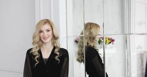 Le modèle femelle blond avec les cheveux bouclés dans le déshabillé noir sourit près du miroir banque de vidéos