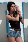Le modèle femelle utilise le dessus noir et les jeans courts Image stock