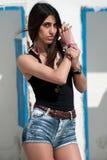 Le modèle femelle utilise le dessus noir et les jeans courts Images stock