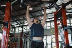 Le modèle masculin musculaire avec le corps parfait faisant la traction se lève photo stock