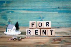 Le modèle miniature de la maison et la lettre en bois textotent : À louer photos stock