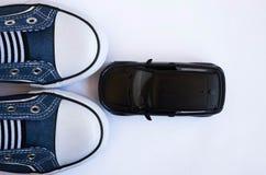 Le modèle noir de SUV devant les espadrilles bleues se ferment  photographie stock libre de droits