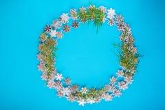 Le modèle saisonnier coloré des flocons de neige, branches d'arbre de Noël sur un fond bleu sous forme de Noël tressent Hiver h image libre de droits